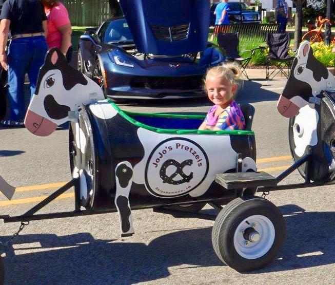 Happy girl rides a tootsie train at Sturgis Fest in Sturgis, Michigan